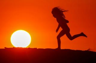 A running child is silhouetted against a red sunset