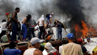 Opposition supporters unload humanitarian aid from a truck that was set on fire after clashes between opposition supporters and Venezuela's security forces at Francisco de Paula Santander bridge on the border between Colombia and Venezuela as seen from Cucuta,