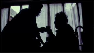 Silhouette of elderly woman being given tea by carer