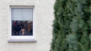 Refugee boy Ramzi Khatoum looks out of the window of a refugee shelter in Clausnitz, eastern Germany, as politicians and journalists visit the home on February 22, 2016.