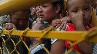 A family in the migrant caravan waits at a gate separating Guatemala from Mexico on 19 October 2018 in Ciudad Tecun Uman, Guatemala