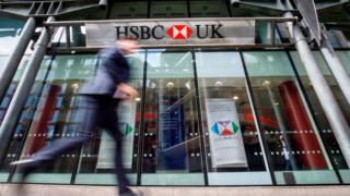 человек проходит мимо банка HSBC