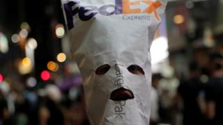 An anti-government protester wears a mask made with a FedEx envelope