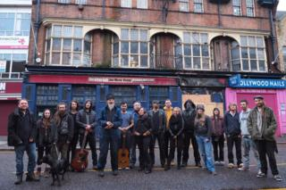 Group of people in front of the derelict pub