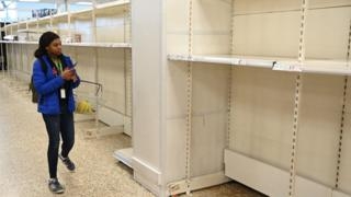 Shopper looks at supermarket shelves left empty after panic buying of toilet rolls