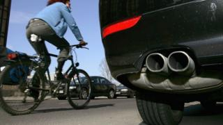 Woman cycling past car in Berlin, file picture