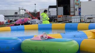 Police at the scene where a seven-year-old girl died after she was blown around 150 metres on a bouncy castle, which is thought to have been swept away by a sudden gust of wind at an Easter fair.