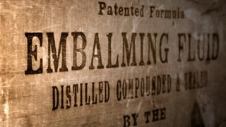 Box with the text 'embalming fluid' printed across it