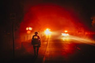 A firefighter walks along a roadside, framed by the red flow of distant lights