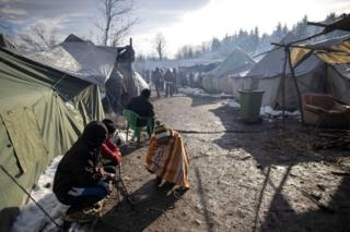 Migrants warm up at the migrant camp in Vucjak near Bihac, Bosnia and Herzegovina, on 6 December 2019