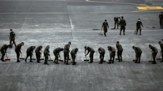 Soldiers sweep the ash covered tarmac at La Aurora International Airport