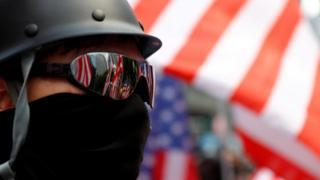Honq Konq-da Amerika səfirliyinin önündə minlərlə etirazçı toplaşıb. Onlar ABŞ bayraqlarını dalğalandırırlar.
