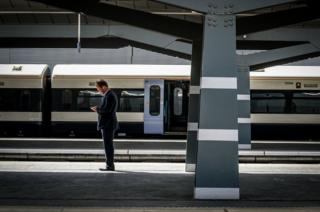 A man standing on a train station platform