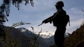 n Indian army soldier is silhouetted against the snow capped mountains of Pakistan administered Kashmir as he guards the the Line Of Control on April 20, 2015 i