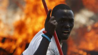 A protester gestures in front of flames in Burundi (2015 picture)