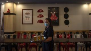 A waitress serves beer at a bar in Seville on 17 May 2020