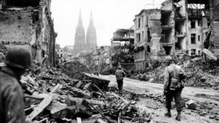 Troops of the 3rd Armored Division, U.S. First Army, advance through the devastation of Cologne, Germany, in March 1945
