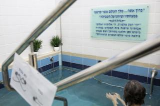 A Jewish woman enters the water of a mikva in Jerusalem on April 17,2019. It is a religious requirement for all married Orthodox women to go to the mikvah, or ritual bath, at night, seven days after their period has finished. It is a way to spiritually purify themselves and has great emotional significance for many women. (Photo by Heidi Levine for The BBC).