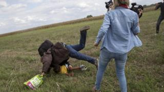 Hungarian camerawoman Petra Laszlo was filmed apparently kicking and tripping up migrants fleeing police, including a man carrying a child. Pictured in Roszke village, Hungary, September 8, 2015.