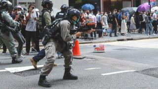 A riot police officer fires his weapon during a protest in Central,