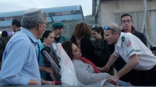An Israeli woman is treated for shock outside supermarket near Ramallah