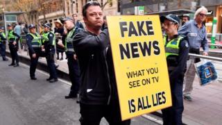 شاب يحمل لوحة لرفض الأخبار الكاذبة