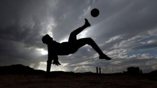 A boy plays football in a youth match in Yemen