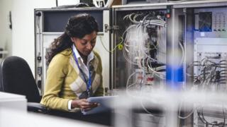 Creative pic of woman checking network servers