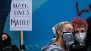 Demonstrators hold a rally and teach-in outside of the Seattle Police Departments East Precinct, which has been boarded up and protected by fencing, on June 8, 2020 in Seattle, Washington.