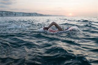 A woman has an early morning swim in the sea with cliffs behind her