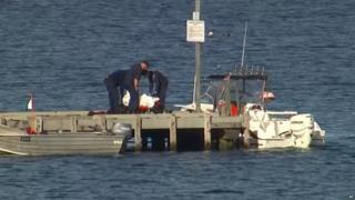 Police carry a body in a bag and place it in on a stretcher on a jetty in Triabunna, off the Australian island of Tasmania