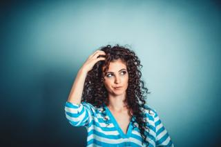 Portrait close-up of a woman wearing a blue and white stripy top, she's looking up, confused, and is standing in front of a blue wall background