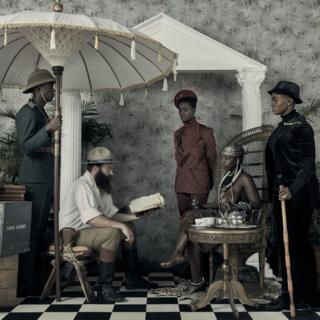 La imagen muestra una escena de los tiempos coloniales: un explorado con un libro y una mujer africana escucha la lectura.