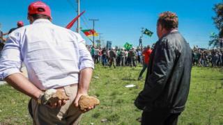 Un homme avec deux pierres aux mains prêt à caillasser l'ancien président.