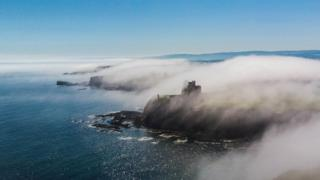 Sea fog by the coast shrouding castle ruins