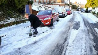Man clears snow in Westbury, Wiltshire, on 2 February 2019