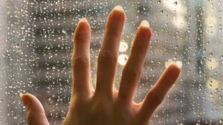 Una persona con la mano sobre una ventana, mientras afuera llueve