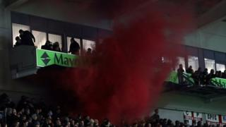 Flares are let off by Crystal Palace fans inside the Amex Stadium