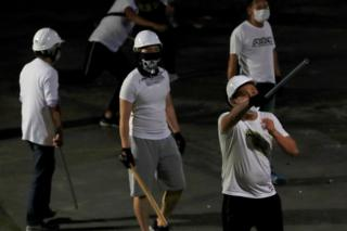 in_pictures Men in white T-shirts with poles are seen in Yuen Long after attacked anti-extradition bill demonstrators at a train station, in Hong Kong, China July 22, 2019.