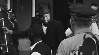 """Pasajeros negros siendo expulsados de una """"sala de espera para blancos"""" en una estación de buses."""