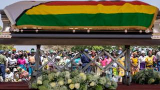 Villagers look at the coffin of late former Zimbabwean president Robert Mugabe lying in state at Murombedzi Growth Point, about 107 km northwest of Harare, Zimbabwe, on September 16, 2019, as people have been accorded the opportunity to view Mugabe's body a week after his death. - The remains of former Zimbabwe president Robert Mugabe were taken to his village for a wake on September 16, a family member said, as his final burial is prepared in about a month. Mugabe died a week ago aged 95 in Singapore, nearly two years after he was ousted in a 2017 coup that ended nearly four decades of increasingly autocratic rule. After a state funeral on September 14 in the capital Harare attended by African leaders, his body went to his rural village of Kutama, 90 kilometres (55 miles) to the west, to allow villagers to pay tribute and bid farewell.