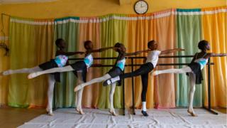 in_pictures Young dancers dressed in matching leotards hold a ballet barre during a class.