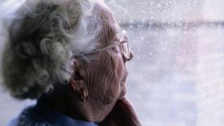An elderly woman looking out of a rain-soaked window