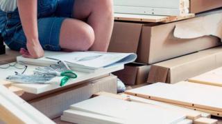 Manual de instrução ao lado de caixas de papelão