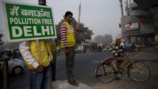 """Volunteers display placards which read: """"We will make a pollution free Delhi"""" during a two-week experiment to reduce the number of cars to fight pollution in New Delhi, India, Monday, Jan. 4, 2016."""