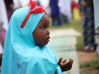 A young girl wearing a blue hijab and red bow cups her hands in prayers.