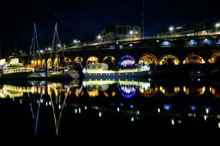 Reflections of boats and lights in water