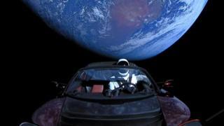 Dalam foto selebaran yang dibagikan oleh SpaceX, sebuah penjelajah Tesla diluncurkan dari sebuah roket dengan seorang pengemudi boneka bernama Starman menuju Mars