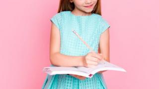 Stock image of a child writing