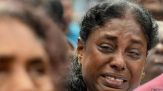 A Sri Lankan Christian devotee cries as she prays at a barricade near St. Anthony's Shrine in Colombo on
